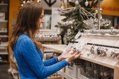 Kvinnan på jul marknadsför att välja garnering och vitt och försilvrar bollar för julgran i nytt år shoppar brunett arkivbilder