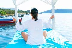 Kvinnan på meditationen på havet seglar utmed kusten, Royaltyfria Bilder