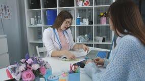 Kvinnan på mottagande i kontoret av en familjdoktor Rådgivning i medicinsk doktors kontor arkivfilmer