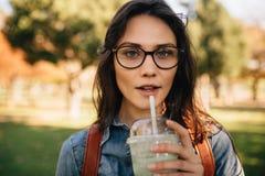 Kvinnan på parkerar att dricka fruktsaft royaltyfri fotografi