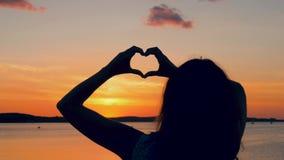 Kvinnan på solnedgången gör en handhjärta stock video