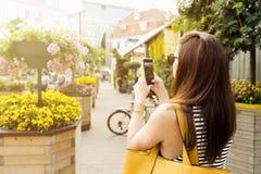 Kvinnan på stad turnerar att ta bilden av härliga kaféblommor med hennes smartphone Arkivfoto