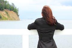 Kvinnan på stranden ser havet, sommartid arkivbilder