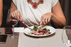 Kvinnan på tabellen äter ny sallad med kött och tomater i en restaurang Arkivbild