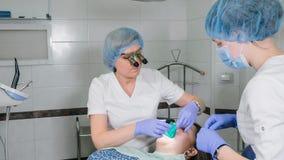 Kvinnan på tandläkarekliniken får tand- behandling för att fylla ett hål i en tand Tand- återställande och sammansatt material Fotografering för Bildbyråer