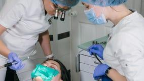 Kvinnan på tandläkarekliniken får tand- behandling för att fylla ett hål i en tand Tand- återställande och sammansatt material Royaltyfri Fotografi