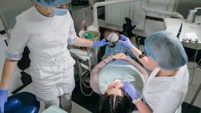 Kvinnan på tandläkarekliniken får tand- behandling för att fylla ett hål i en tand Tand- återställande och sammansatt material Royaltyfri Bild