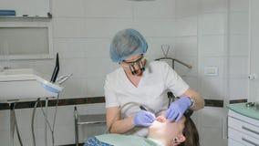 Kvinnan på tandläkarekliniken får tand- behandling för att fylla ett hål i en tand Tand- återställande och sammansatt material Royaltyfri Foto