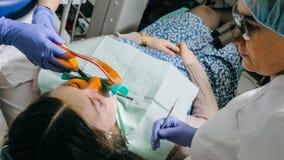 Kvinnan på tandläkarekliniken får tand- behandling för att fylla ett hål i en tand Tand- återställande och sammansatt material Royaltyfria Foton