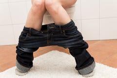 Kvinnan på toaletten lider om blodstockning arkivfoton