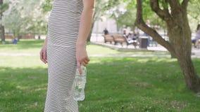 Kvinnan parkerar in dricksvatten från flaskan stock video