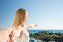 Kvinnan pekar med hennes finger till havet från ett balkony i sommarferie arkivbild