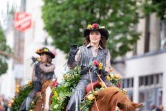 Kvinnan piskar in likformign på en häst arkivbild