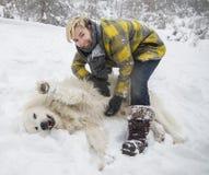 Kvinnan plaskar med en vit hund i snö royaltyfri foto