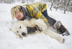 Kvinnan plaskar med en vit hund i snö arkivfoto