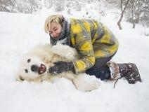 Kvinnan plaskar med en vit hund i snö royaltyfria bilder