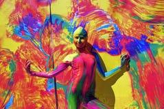 Kvinnan poserar för fotos på färgrik bakgrund Arkivbild