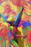 Kvinnan poserar för fotos på färgrik bakgrund Fotografering för Bildbyråer