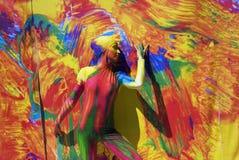 Kvinnan poserar för fotos på färgrik bakgrund Royaltyfri Bild