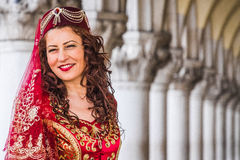Kvinnan poserar under bågar av dogens slott, den Venedig karnevalet Fotografering för Bildbyråer