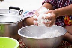 Kvinnan pressar kokosnötkött för att få kokosnöten mjölkar Royaltyfri Bild