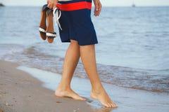 Kvinnan promenerar den sandiga stranden Royaltyfria Bilder