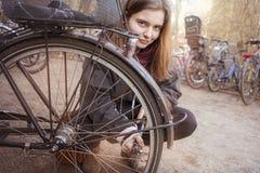 Kvinnan pumpar upp gummihjulen av hennes cykel royaltyfri foto