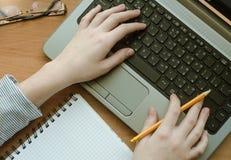Kvinnan räcker arbete på en bärbar dator Arkivfoto