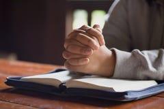 Kvinnan räcker att be till guden med bibeln att tigga för förlåtelse och tror i godhet Kristen livkrisbön till guden arkivfoto