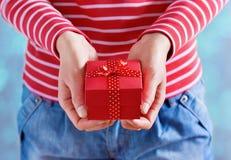 Kvinnan räcker att rymma en gåva eller en gåvaask med pilbågen av det röda bandet för valentindag Arkivbilder