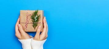 Kvinnan räcker att rymma en julgåvaask Julklappar och nytt år handgjort royaltyfri fotografi