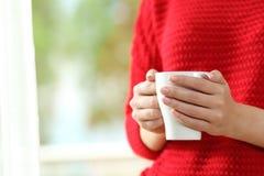 Kvinnan räcker att rymma en kaffekopp Arkivfoton