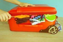 Kvinnan räcker att sätta kläder i resväskan, closeup Resväska med olik saker som är förberedd för lopp Royaltyfri Foto