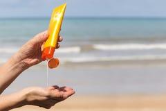 Kvinnan räcker att sätta sunscreen från en suncreamflaska arkivfoto