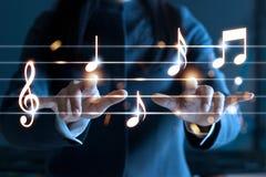 Kvinnan räcker att spela musikanmärkningar på mörk bakgrund, Arkivbild