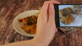 Kvinnan räcker att ta foto av matställemat vid smartphonen Kvinnan tar bilder av mat closeup stock video
