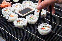 Kvinnan räcker att ta philadelphia sushi. Arkivfoton