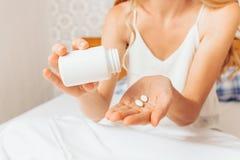 Kvinnan räcker att ta preventivpillerar från bankerna och att sitta i säng och avgiften arkivfoto