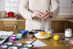 Kvinnan räcker avbrott av ett ägg för att göra muffin royaltyfria bilder