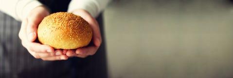Kvinnan räcker bakat bröd för innehavet nytt Bulle kaka, bageribegrepp, hemlagad mat, sunt äta kopiera avstånd baner arkivfoton