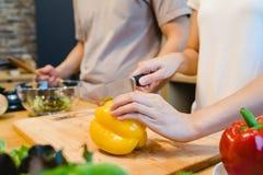 Kvinnan räcker bitande spansk peppar i köket Härliga lyckliga asiatiska par lagar mat i köket Arkivfoton
