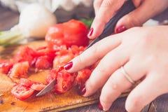 Kvinnan räcker bitande tomater med suddiga grönsaker i bakgrunden tonat Royaltyfri Fotografi