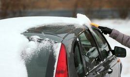 Kvinnan räcker borstasnow från en bil Arkivbild