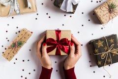 Kvinnan räcker den hållande asken för julferiegåvan den röda pilbågen på den dekorerade festliga tabellen Fotografering för Bildbyråer