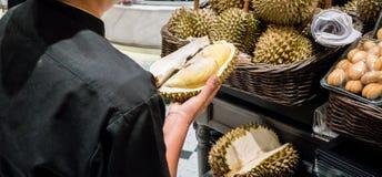 Kvinnan räcker den hållande durianen med det skarpa thronskalet, når han har klippt Royaltyfri Fotografi