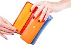 Kvinnan räcker den hållande flerfärgade plånboken royaltyfria bilder
