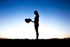 Kvinnan räcker den hållande hjärtakonturn på kontursolnedgång royaltyfria foton