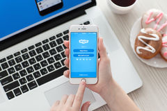Kvinnan räcker den hållande iPhonen 6S Rose Gold med app Skype Arkivbilder