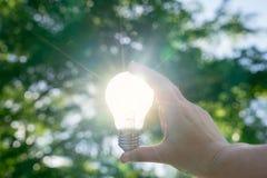 Kvinnan räcker den hållande ljusa kulan med sol- energi eller termisk ener arkivfoto