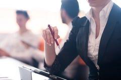 Kvinnan räcker den hållande pennan på affärsmöte Royaltyfria Foton